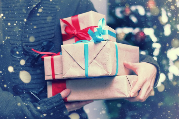 A person carries a stack of wrapped gifts.