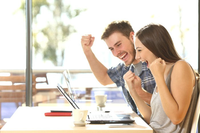 Young man and young woman smiling and holding clenched fists up while looking at a laptop screen