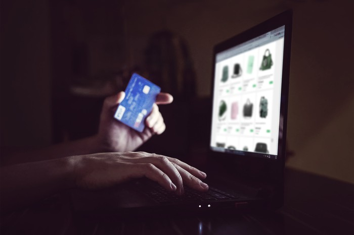 A person holds a credit cars near a computer in the dark.