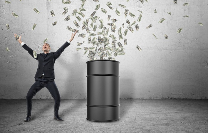 Money bursting out of a black barrel on a concrete floor and a happy businessman in a celebratory stance next to it.