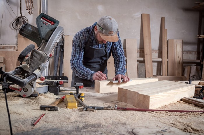 A carpenter measures wood on his work table, with circular saw and other tools nearby.
