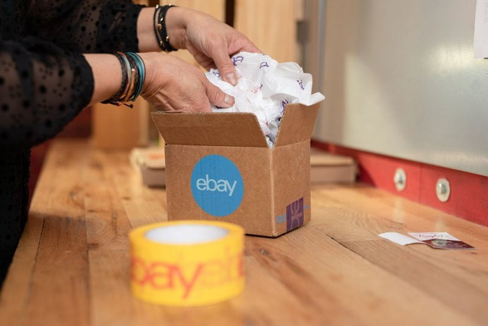 A person placing an item in a cardboard box with an eBay logo.