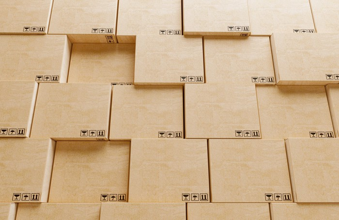 A wall of shipping boxes stacked to resemble a Jenga puzzle.