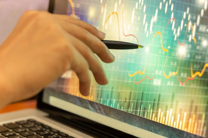 Hand holding pen pointing at stock graph displayed on a laptop screen