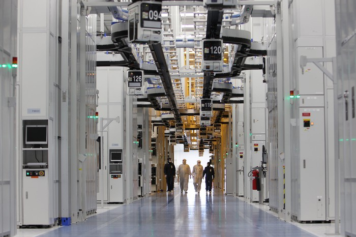 Four employees walking down a long corridor in a Texas Instruments' manufacturing facility.