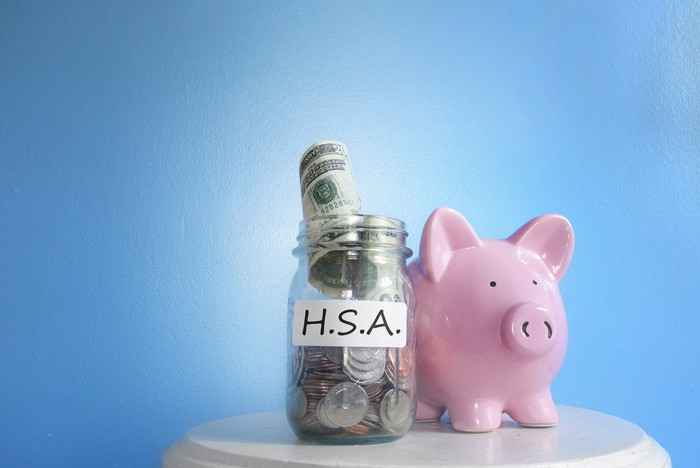 Glass jar full of coins and bills with H.S.A. on label next to a piggy bank.