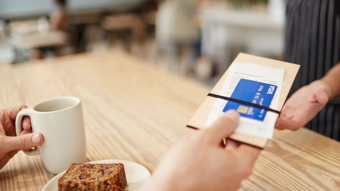 A person handing over a restaurant check with a Visa credit card attached to it.