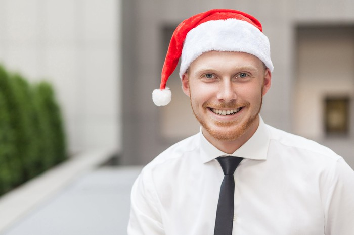 Smiling man in collared shirt and tie wearing Santa hat