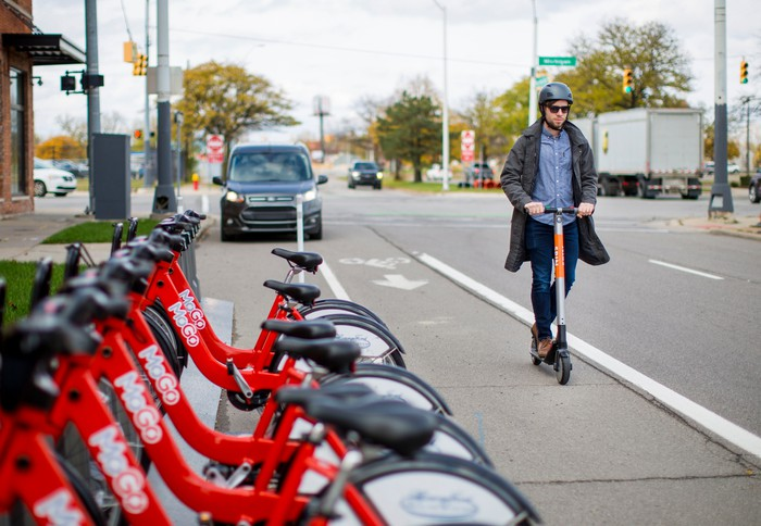 Man riding a scooter in front of a row of parked bikes.