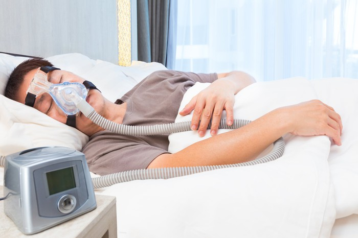 Man sleeping with CPAP machine on face.