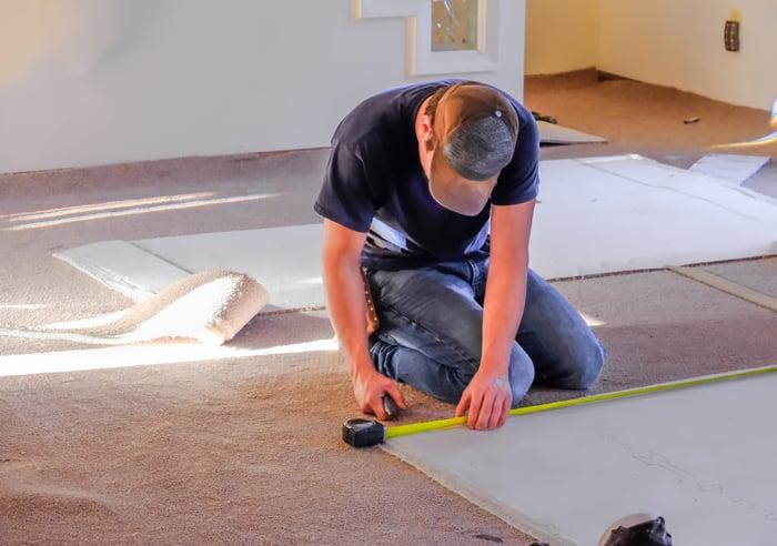 A contractor installing carpet