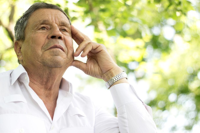 Older man wearing white shirt with serious expression in outdoor setting