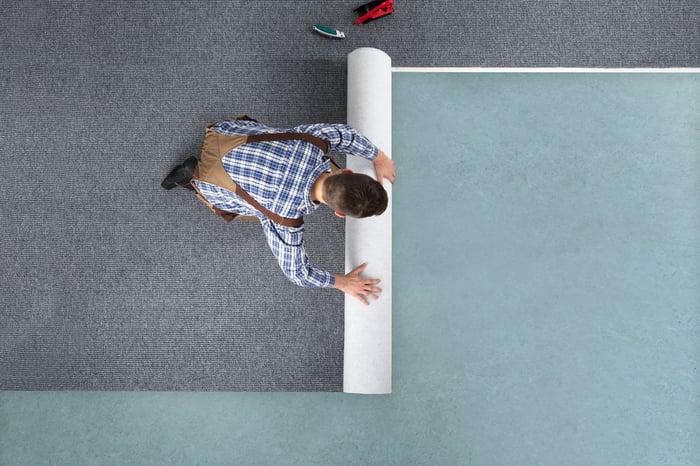 Man installing carpet on floor