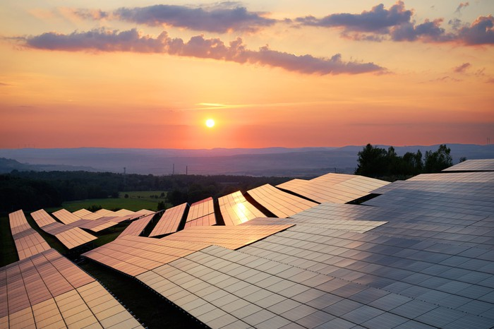 Solar panels in a field under a sunset