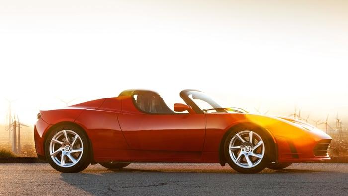Red Tesla Roadster on a road in a desert landscape near sunrise or sunset.
