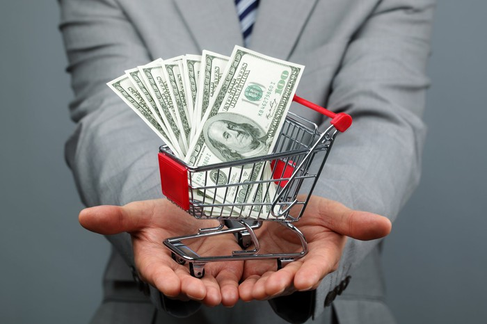 A man holds out a tiny shopping cart filled with hundred dollar bills.