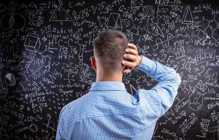 Man, with his right arm on the back of his head, looking at equations on a chalkboard.
