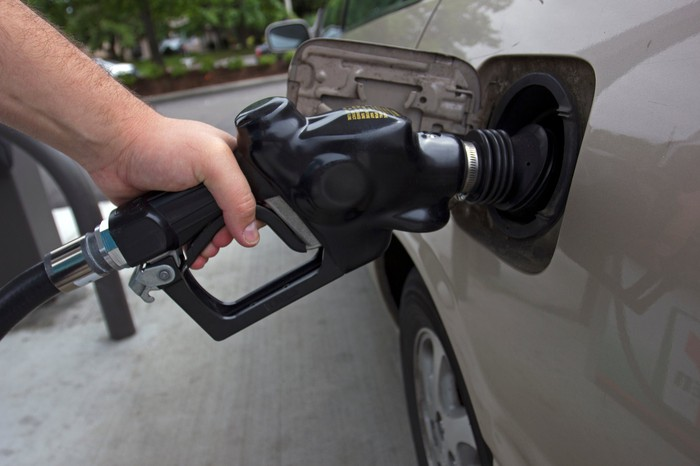 A person holding a gasoline nozzle while filling up their car at a gas station.