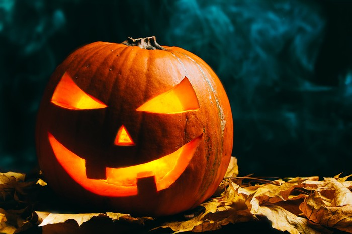 A pumpkin with a scary carved face that has a light source inside of it.