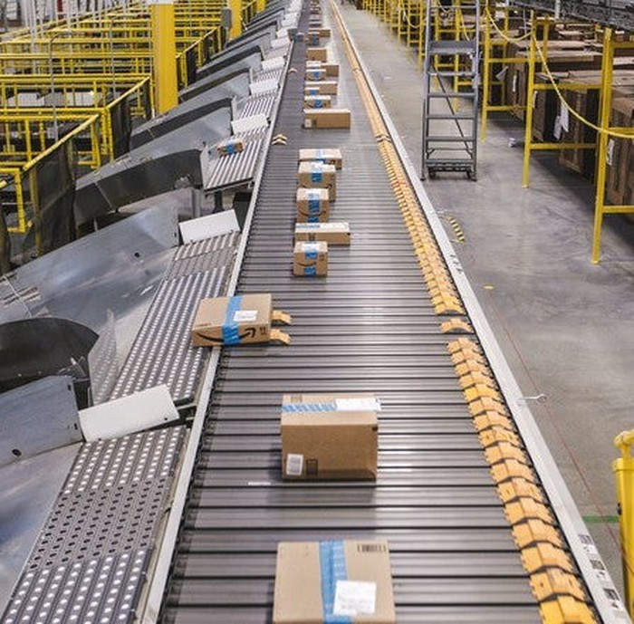 Packages on a conveyor belt in an Amazon fulfillment center.