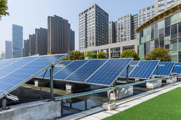 Rooftop solar panels on an office building, with modern office buildings in the background.