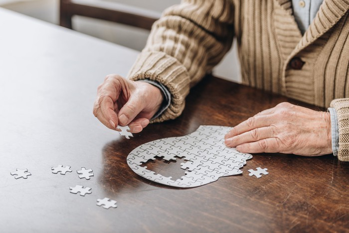 An elderly senior assembling a jigsaw puzzle in the shape of a head with a few pieces around the brain missing.