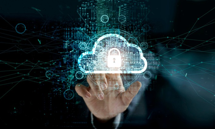 A man touches the image of a cloud with a padlock icon in its center on a screen to illustrate network security.