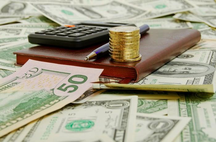 Una calcolatrice, una penna e una pila di monete siedono in cima a un mucchio sparso di valuta americana.