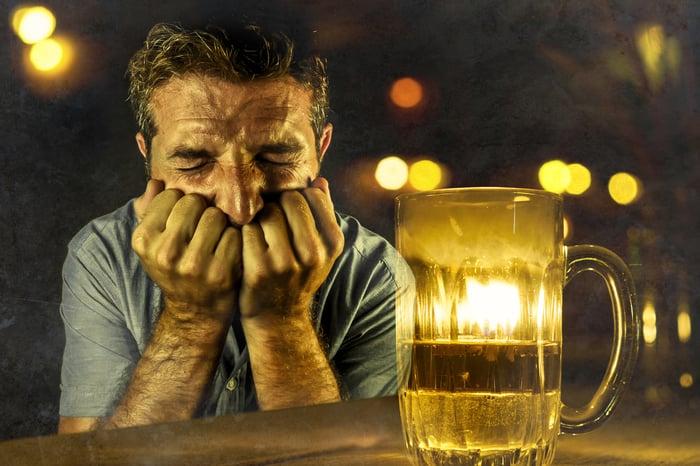 Man grimacing in front of beer mug