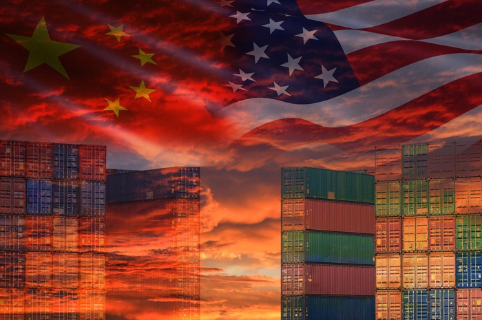 Silhouette of Chinese and American skyscrapers, with the flags of the U.S. and China hovering above