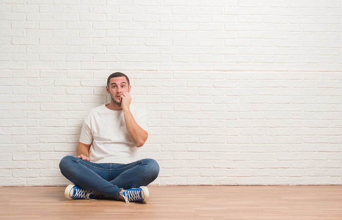 Man in jeans and t-shirt sitting against a white brick wall, biting his nails