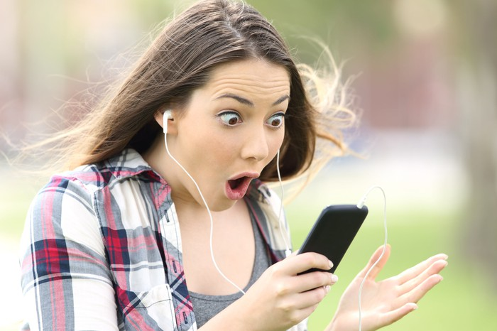 A young woman wearing headphones stares in wide-eyed amazement at her phone.