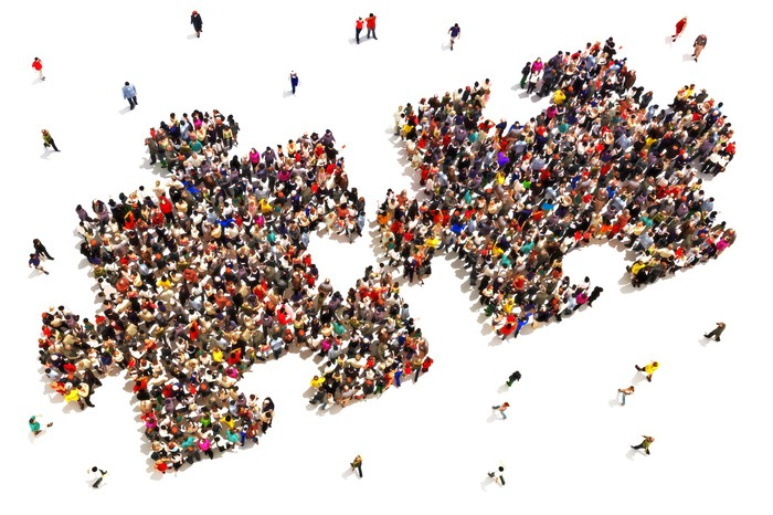 A distant view of a large crowd arranging itself into the shape of two large puzzle pieces.