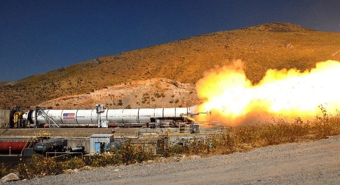 Flames shooting out of the bottom of a solid rocket motor during a ground test.