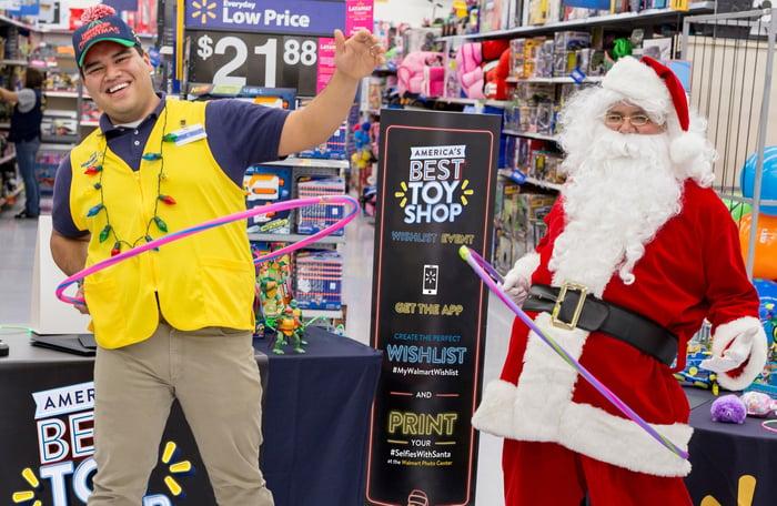 A Walmart employee and Santa standing at a holiday display
