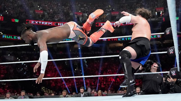 A wrestler plants a flying kick on another in the ring.
