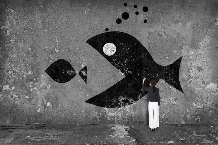 A person drawing a picture of a big fish eating a smaller fish.