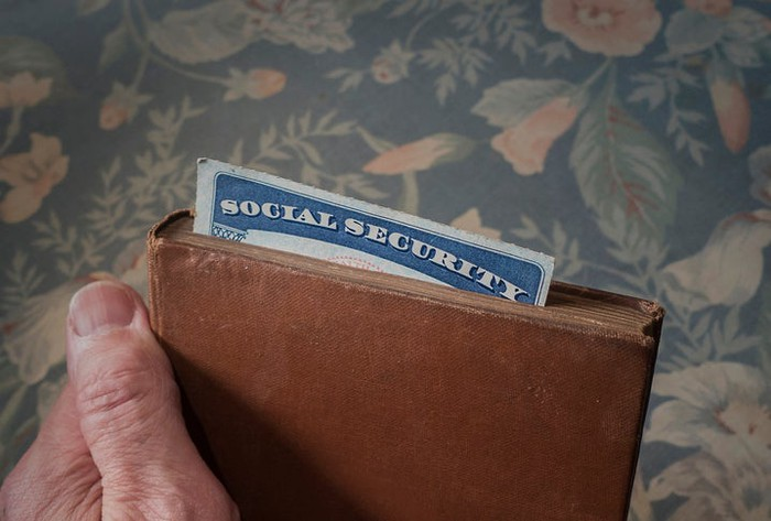 Social Security card sticking out of a book being held by a senior in front of a floral background