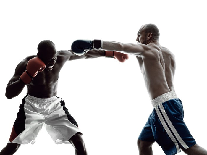 Two boxers facing off, one dressed in red shorts and the other wearing ones in blue.