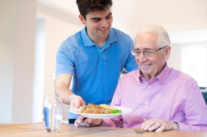 Young man placing plate of food in front of smiling older man