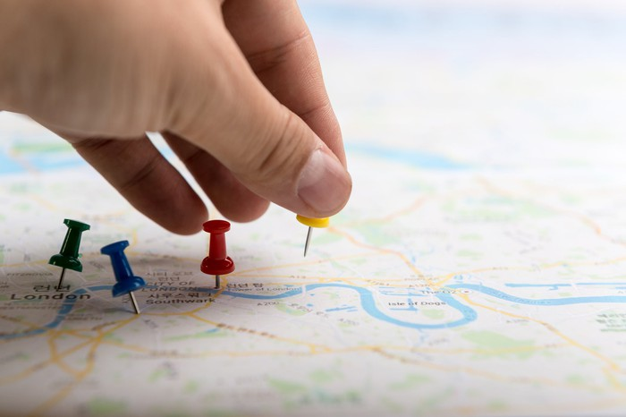 Person putting pins in a roadmap