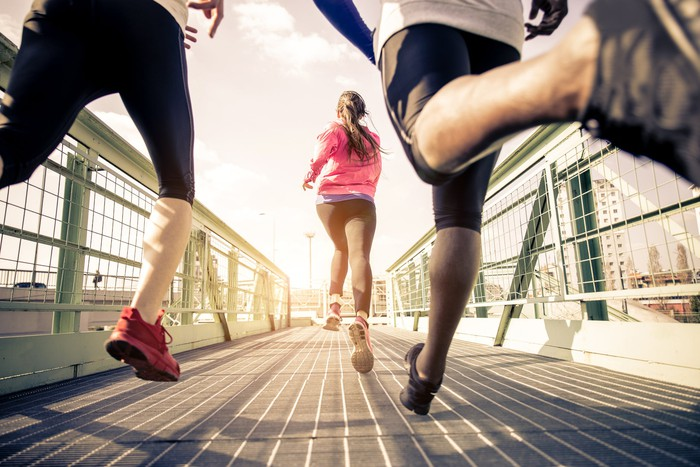 Three people running on a bridge in workout gear.