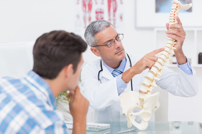 Physician showing a patient a human spine model