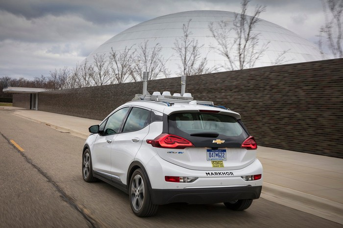 White General Motors vehicle on an empty road with antennas and sensor equipment on the roof.