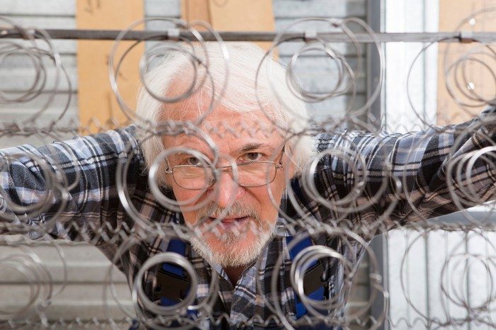 Man looking at a mattress wire frame.