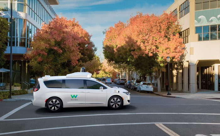 Google Waymo self-driving minivan on a street with fall foliage in the background.