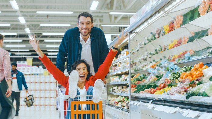 A man pushing an excited woman in a shopping cart through a grocery store