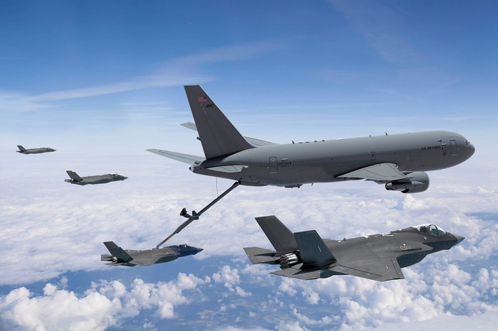 Boeing's tanker aircraft surrounded by fighters awaiting refueling.