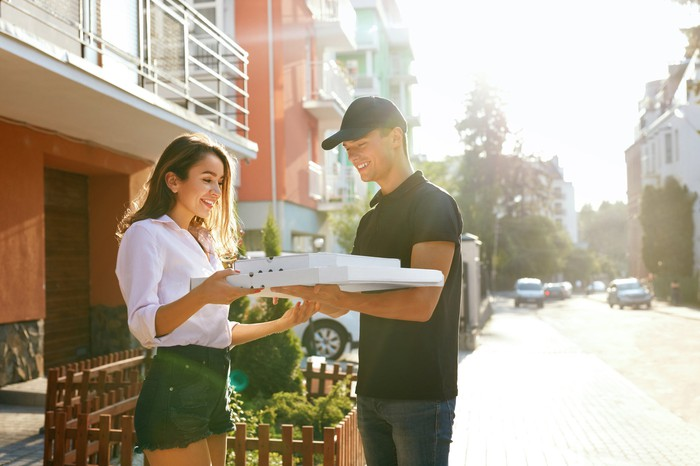A young woman receives a food delivery, meeting the delivery man on the street and smiling.