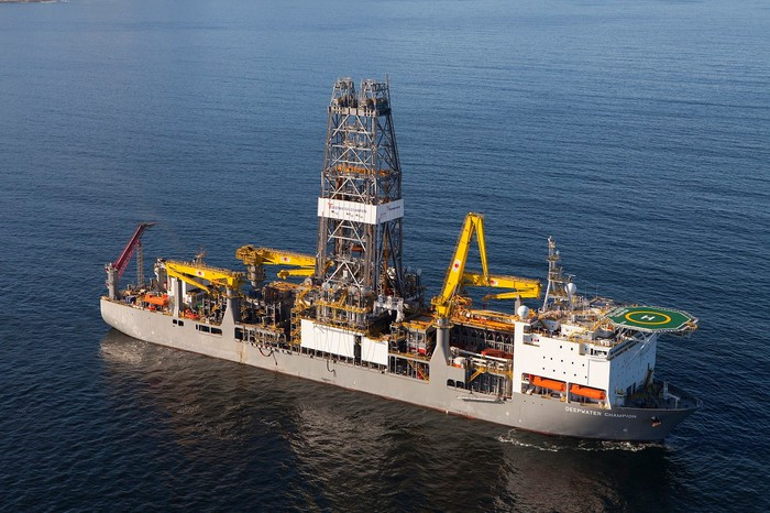 Gray drillship with tower, cranes, and helipad on calm water.